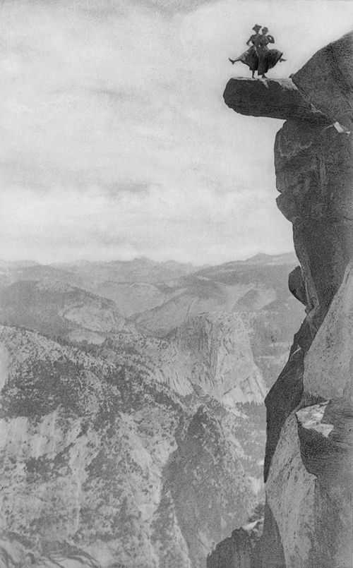 Two women dancing 3000ft above the valley on an overhanging rock at Glacier Point, California. 1900s.