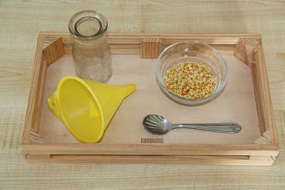Spoon: pour corn kernels from glass vessel to glass dish, place funnel into glass vessel, use spoon to fill funnel with kernels:
