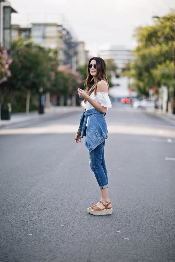 woman in white off the shoulder top, cuffed capri jeans, platform light brown sandals, denim jacket tied around waist and aviator sunglasses