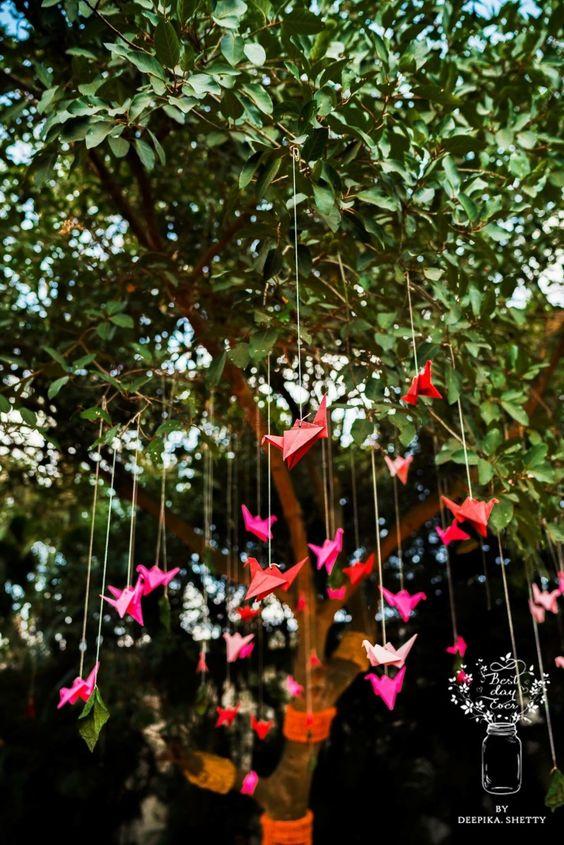 Pretty origami birds décor hanging from a tree | WedMeGood| #wedmegood #indianweddings #origami #birds #decor #hangingdecor #tree #treedecor #DIYDecor #colourful