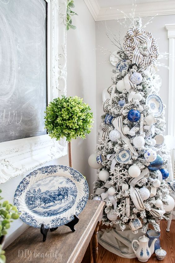 My blue and white Christmas tree has a French farmhouse feel. I've hung vintage dishes and teacups from my tree, along with plenty of handmade ornaments! Come take a closer look at DIY beautify! #blueandwhite #christmastree #farmhouse