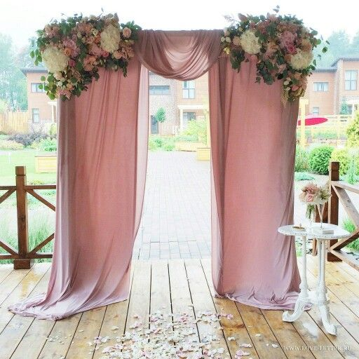 Wedding ceremony drapery with floral arbor. Love the dusky pink fabric.