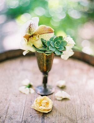 Orchids and roses and echevarias in goblets.