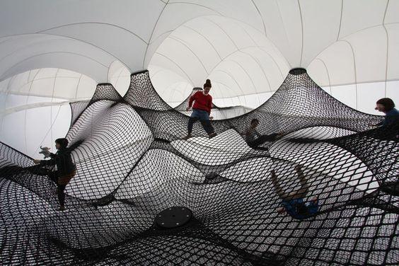 Voici un projet ludique sur l'architecture exposé à travers une installation itinérante. Cette aire de jeu gonflable dispose d'une grande coquille légère en forme de bulbe qui contient une série de filets tissés à l'intérieur sur plusieurs niveaux.  Les visiteurs sont invités à grimper, explorer et jouer sur ces filets au sein de cette sphère aérée et lumineuse tel un château gonflable pour adultes.