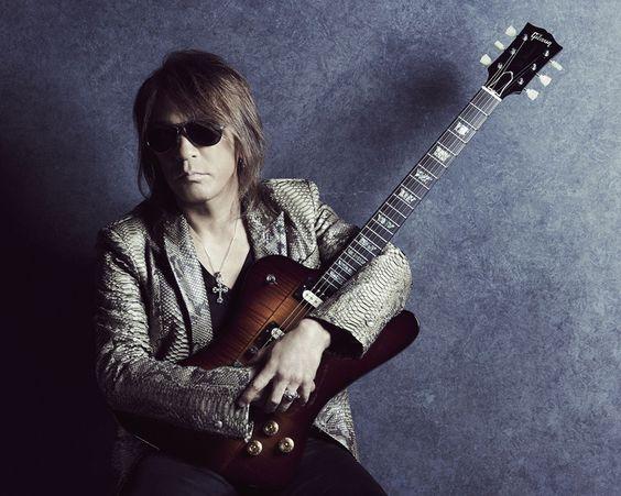ギターを抱きかかえる松本孝弘