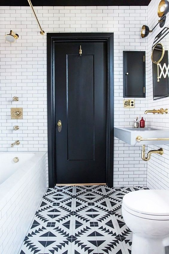 Monochrome bathroom with floor to ceiling subway tile, printed floor tiles,  and gold accents