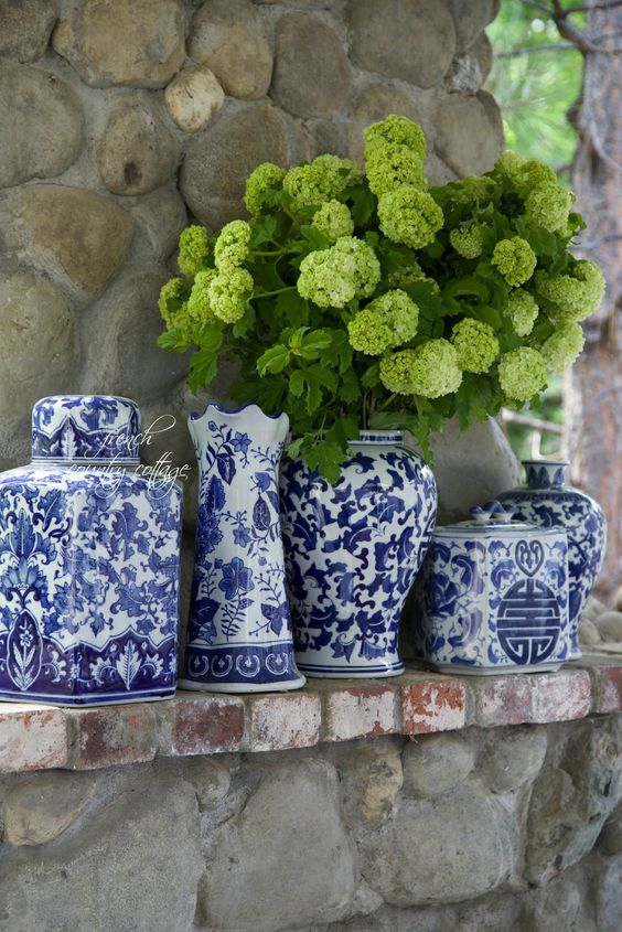 blue and white ginger jars and vases with Snowball Viburnum flowers-stone mantel/outdoor fireplace: