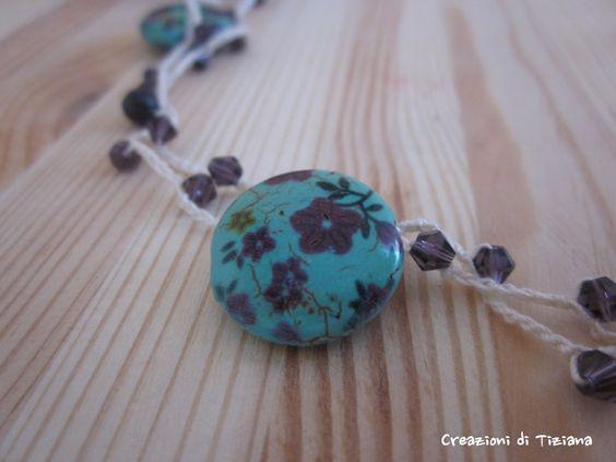 Dettaglio collana all'uncinetto con pietre dure viola scuro e pietre rotonde azzurre con fiori