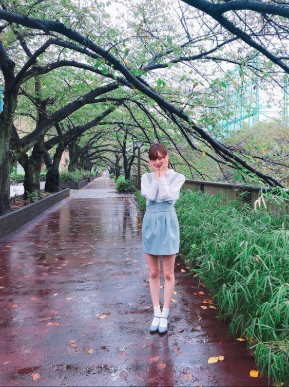 ミニスカートをはいた桜並木の中に立つ梅澤美波の画像