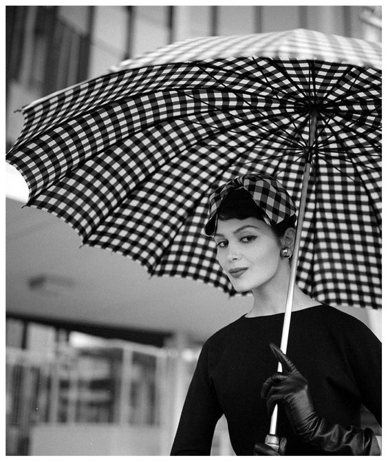 Isabella Albonico in a a black and white check silk hair bow by Sally Victor and oversize umbrella by Uncle Sam, photo by Nina Leen, March 1958