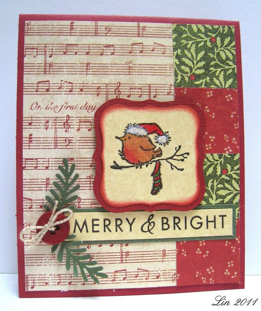 "Lin's card -supplies: red and green Core'dinations and parchment cardstock, design papers from The Paper Studio (music) and graphic 45's ""Christmas Past Collection"", Penny Black 30-058 Jolly Friends, and Hero Arts CL460 Joy to All, Versafine onyx black ink, Prisma colored pencils, glue pen and prisma glitter, red button, natural twine, punched leaves, Nesties Labels one dies, fired brick distress ink."