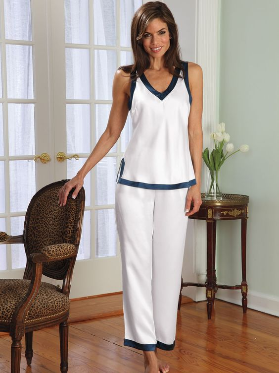 The perfect setting to make you feel like a star, this stunning look is designed to highlight you and only you. Made of scintillating pure silk charmeuse in White with Navy, it gives you a glow as flattering as candlelight. Seductively styled with a plunging V-neck, the bare little chemise and pajama top embody all the glamour of the matching kimono. Straight-leg pants have comfy elastic waist. Imported. Hand wash or dry clean.
