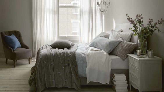 Shabby Chic-inspired Grey Bedroom with Textured Cushions and Throws