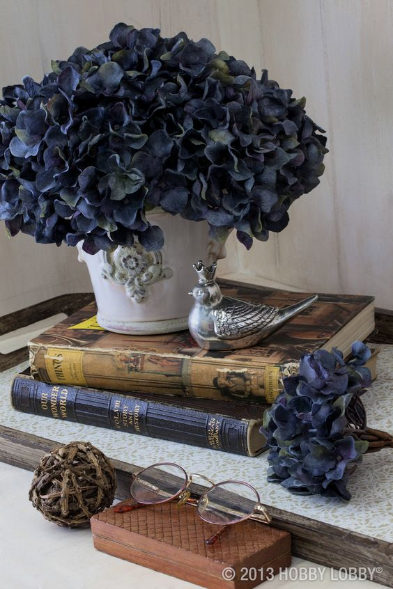 Use faux flowers and vintage books to make a beautiful side table display.