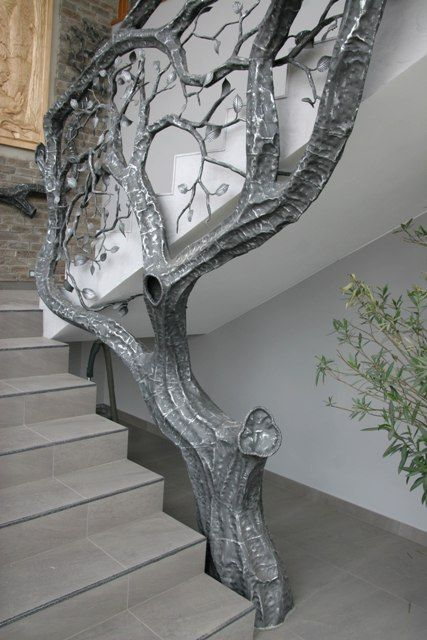 Tree railing / bannister in silver, growing beside staircase.: