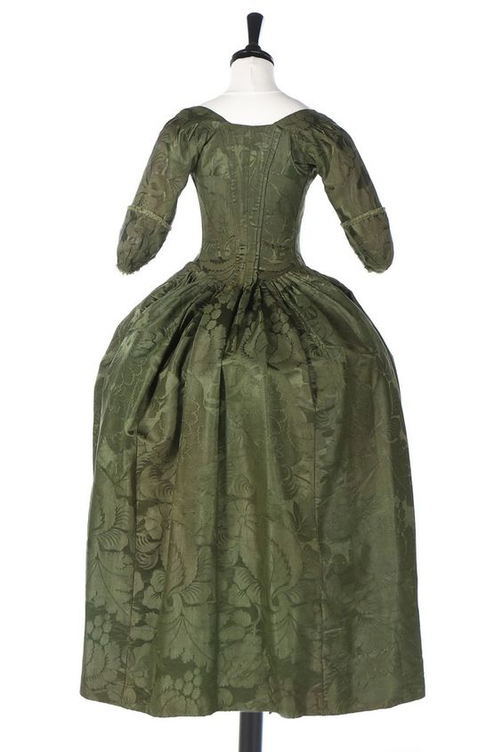 Rear view, robe à l'Anglaise, England (Spitalfields), ca. 1770, fabric: ca. 1743. Forest-green silk damask, woven with large scale flowerheads, berries and leaves, with ribbon-tied front bodice, cuffs edged in self-fringing.