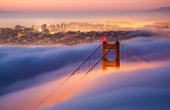 Sunrise in San Francisco, with the famous fog rolling in over the Golden Gate bridge.