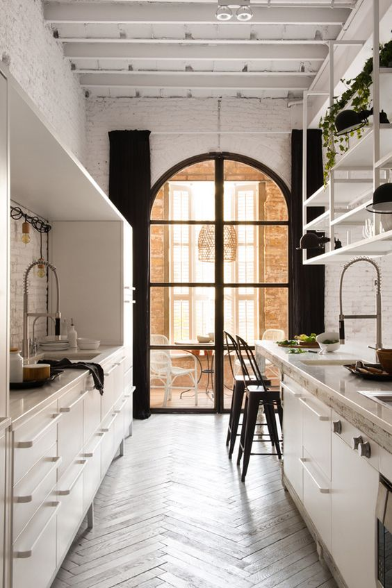 Barcelona loft, fabulous Eat-in kitchen with unusual arched window and herringbone floor. Interesting blend of modern, classical and rustic