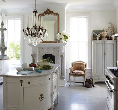 Romantic and feminine white kitchen with farmhouse style, fireplace, crystal chandelier, delft tiles, and unique repurposed island. Design by Annie Brahler Smith. #whitekitchen #countrykitchen #european #frenchcountry