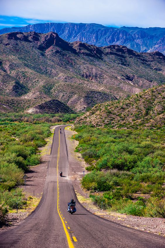 Motoryclists ride down a long straight road (FM 170, the Camino del Rio), Big Bend Ranch State Park, Texas