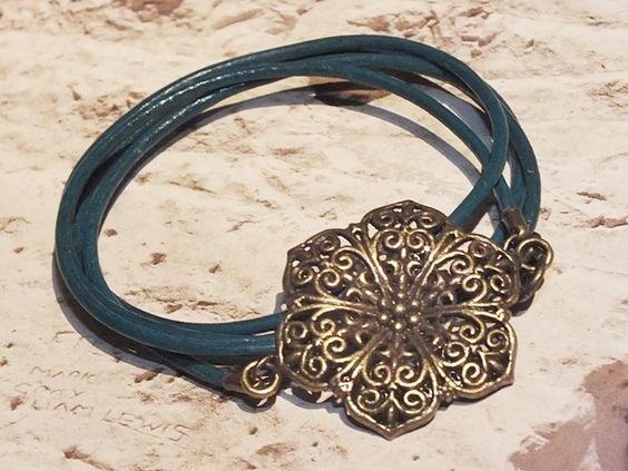 Tolles Leder Wickelarmband im Vintage Stil angefertigt aus petrolfarbenen Rundlederriemen und einem Metallamulett in Blütenform.