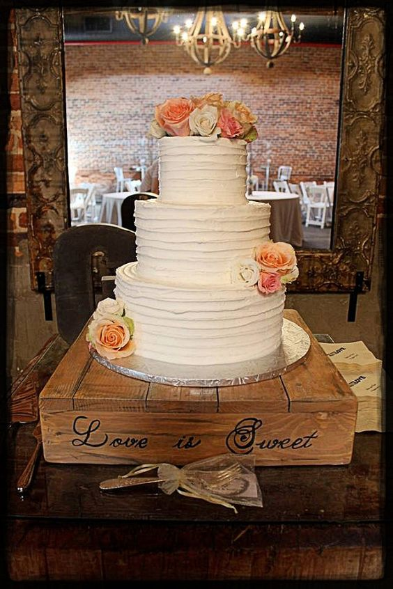 Love the wooden stand underneath the cake