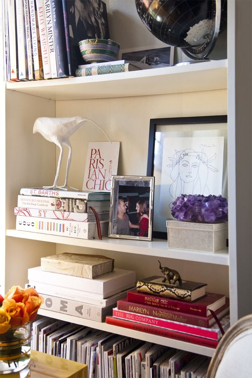 bookshelf styling. A collection of magazines on the bottom shelf.
