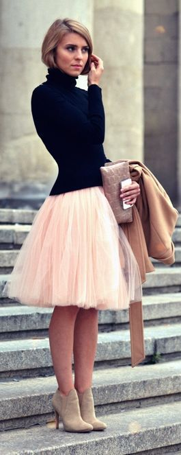 Black turtleneck over pink tulle skirt, beige bootilettos, beige clutch, camel coat, sandy blonde bob: