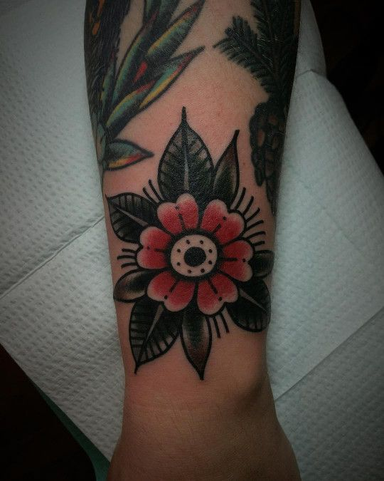 Traditional Simple Flower Tattoo Consisting Of Red And Black Colors Inked On The Left Wr Traditional Tattoo Flowers Traditional Tattoo Wrist Traditional Tattoo