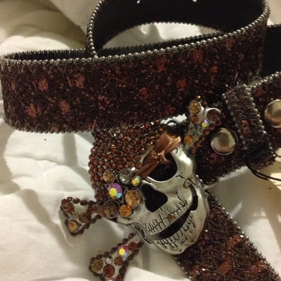 "Brown GLITTER, Lace & SWAROVSKI crystal SKULL Belt STATEMENT BELT w/ENCRUSTED SKULL front & Center! BROWN GLITTER & LACEY 1.25"" wide with Silver METAL BUCKLE covered in light & dark brown & iridescent crystals. Buckle is 3"" x4"" wide. Multiple holes for size customization. Black underside, silver  ""ball"" edge. Bought in local boutique that is no longer there but tag attached. Have red one in 36"" at listing time also for sale. unknown Accessories Belts"