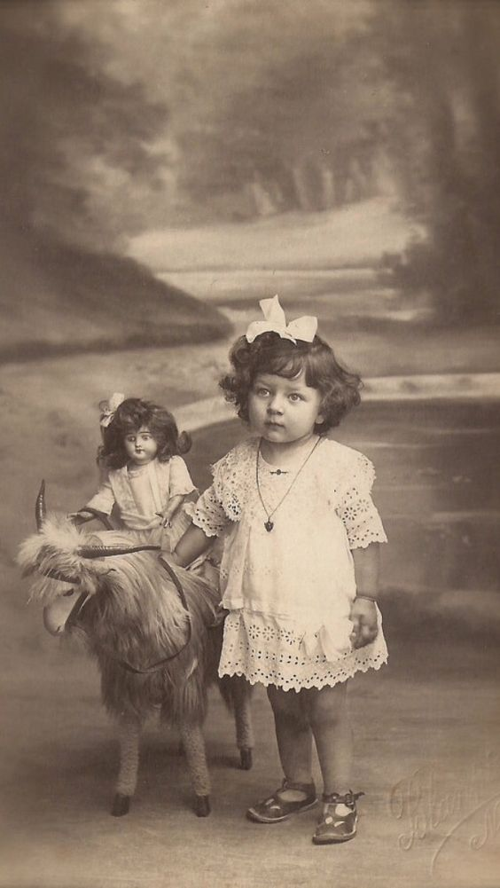 Antique photo of a little girl with her doll.. the doll is riding on a stuffed lamb toy.