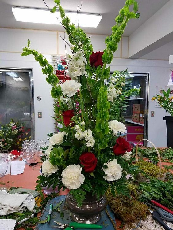 A Tall Funeral Piece With Res Roses White Carnations Green Bells Of Ireland And White Stock Flowers Flower Delivery White Carnation Order Flowers Online