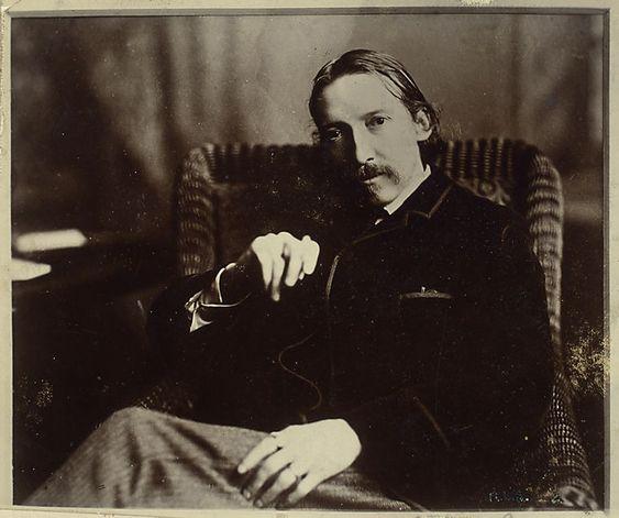 R. L. Stevenson (seated on chair with left leg over knee, left hand on left…