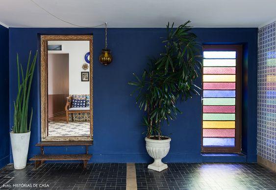 Entrada de casa tem clima marroquino com pendente e porta de vidro colorida.