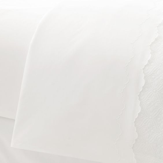 A classic 500-thread-count, 100% Egyptian cotton percale flat sheet in crisp white gets a feminine flourish with a delicately embroidered double-scallop hem. Crafted in Italy by skilled artisans, Isabella White is a lovely addition to any bed. Embroidery threads on Isabella have been matched for use with our jacquard and striée woven duvet covers and shams.   Pair with our  Lia White Fitted Sheet .   • 100% Egyptian cotton percale.  • 500 thread count.  • Double scallop embroidery.  •