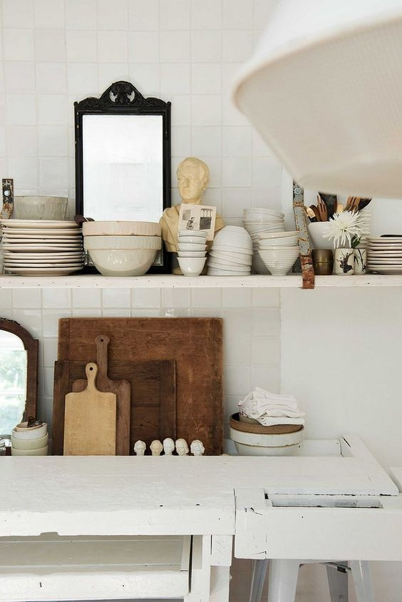 Cool chic in a kitchen with white open shelves stacked with vintage pottery and rustic treasures. Design by #LeanneFord. #moderncountry and #farmhousestyle in this vintage #bohokitchen