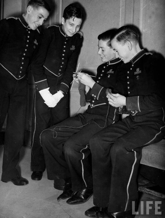 Pageboys knitting garments during drive to provide goods to servicemen during the war.: