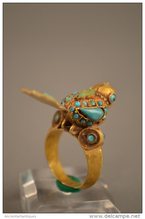 A  Gold Bird Ring, Middle East, circa 600-400 B.C Gold Ring with Inlaid Termini in the Form of Seated Bird.