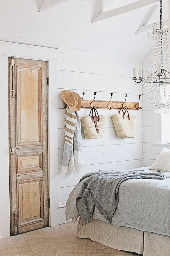 French farmhouse style decor from Dreamy Whites in a charming bedroom with vintage hook rack, old door, and French market baskets. #frenchfarmhouse #farmhousestyle #farmhousedecor #modernfarmhouse #bedroomdecor #bedroomideas #shiplap #vintagestyle #whitedecor #dreamywhites #decoratingideas #countryliving #frenchstyle #fixerupperstyle