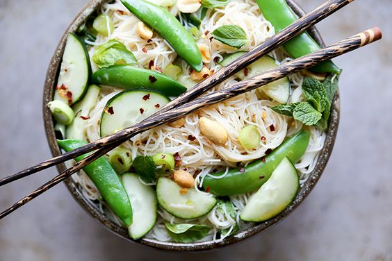 An easy recipe for a vegan and gluten free rice noodle salad with snap peas, cucumbers, scallions, fresh herbs and peanuts.