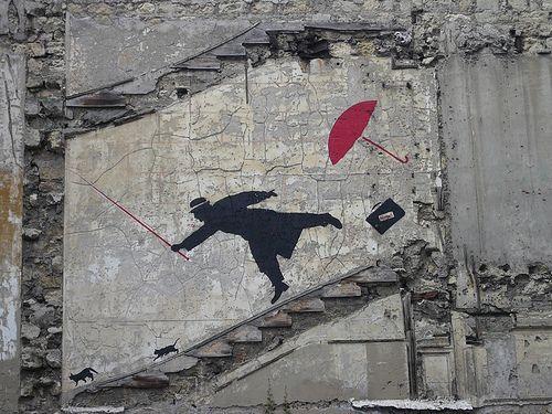 À Paris la silhouette noire d'un homme en imperméable coiffé d'un chapeau. Oeuvre de Nemo, peintre pochoiriste français. Photo de Balavenise.