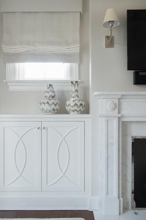 Morgan Harrison Home A White Roman Shade Hangs Over A Built In White Mullion Cabinet Topped With W Marble Fireplaces Freestanding Fireplace Fireplace Mantels