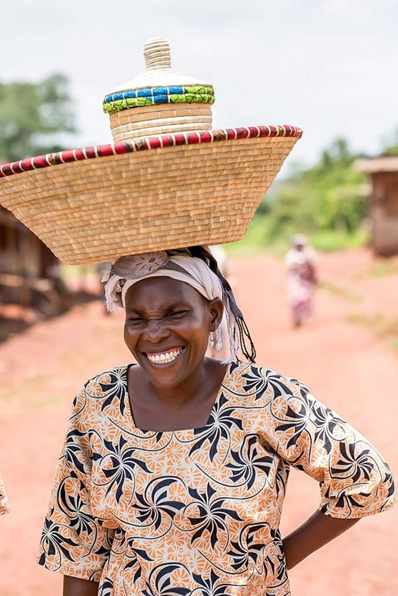 An woman from Africa carrying her artisan products in her head with a gorgeous smile