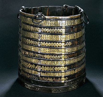 Oseberg viking bucket. This bucket was one of several found on on the ship. Made out of yew wood it is surrounded by decorative brass fittings and held together with iron hoops. A wooden ladle and 6-7 wild apples were found inside it.