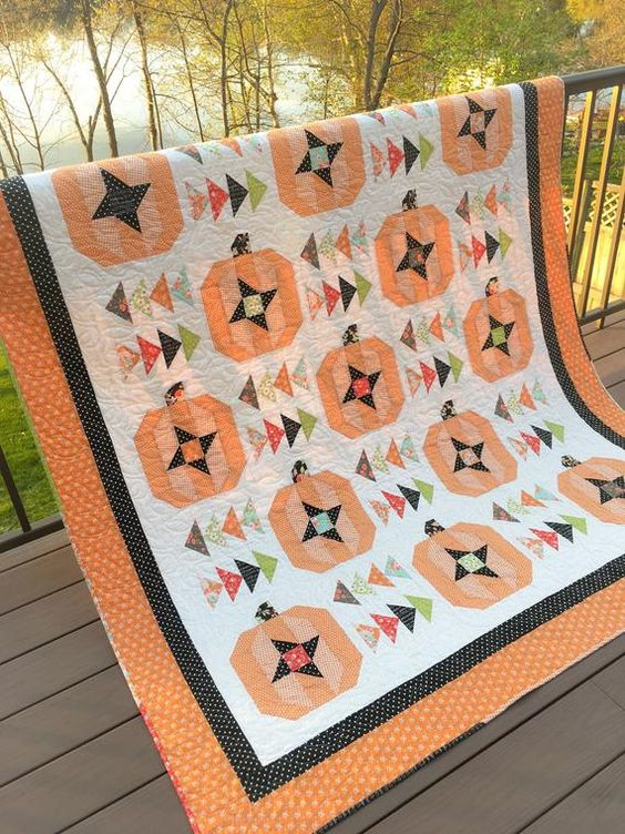 """Fall Flight is a 66"""" x 76"""" throw quilt featuring Carried Away Quiltings signature pumpkin block, alternating with scrappy flying geese blocks. The sample quilt features fabric by Fig Tree & Company for Moda, with the orange prints coming specifically from the Farmhouse II collection. Eight fat"""