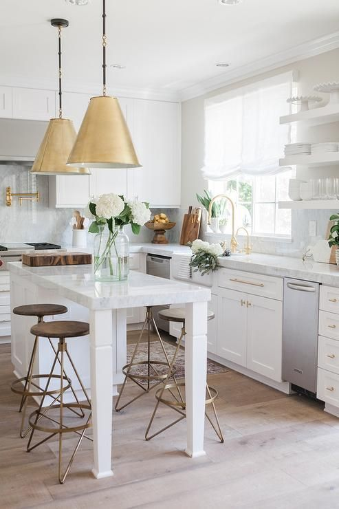 White classic kitchen with Shaker cabinets, #brasshardware, and brass pendant lights over island