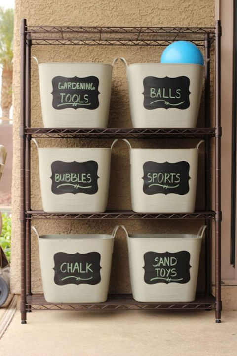 Keep your yard clutter-free by placing bins with adhesive chalkboard labels onto a sturdy bronze shelf. Click through for more on this and other smart storage ideas for toy organization.