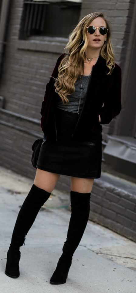 Edgy winter outfit styled with velvet bomber jacket, leather mini skirt, and black over the knee boots