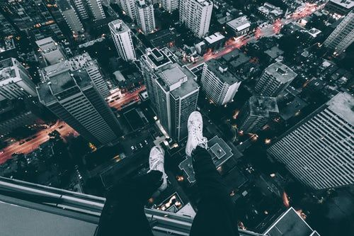 Aerial Photography Of Man Sitting On Top Of Building With High Rise Buildings View At Daytime Building Photography Building Aesthetic Photo