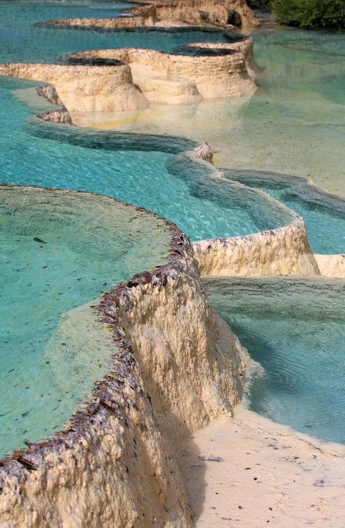 """Pamukkale, meaning """"cotton castle"""" in Turkish, is a natural site in Denizli Province in southwestern Turkey. The city contains hot springs and travertines, terraces of carbonate minerals left by the flowing water. It is located in Turkey's Inner Aegean region, in the River Menderes valley"""